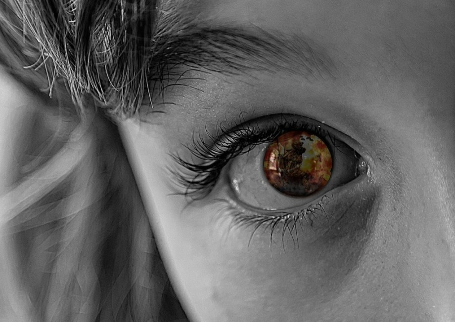 Close up of a child's eye with reflection of an explosion