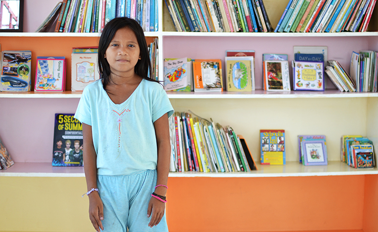 Young Filipina girl standing in front of bookshelves