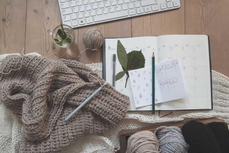 A planner covered by a sweater and pencil
