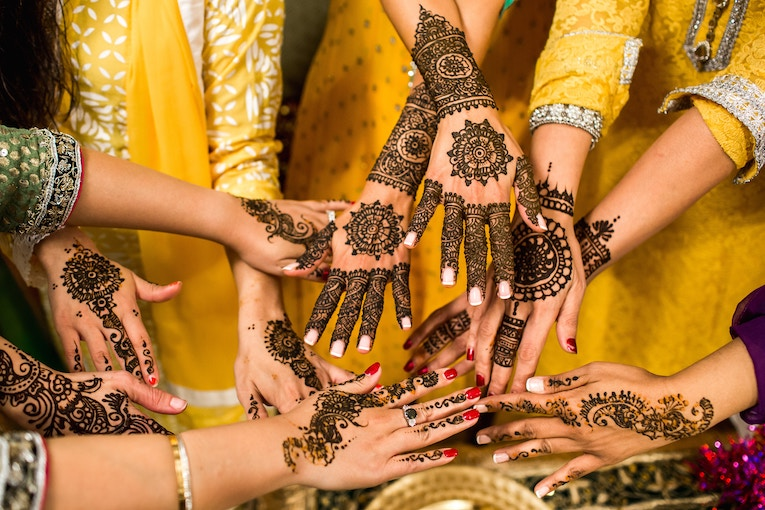 Women's hands covered in henna