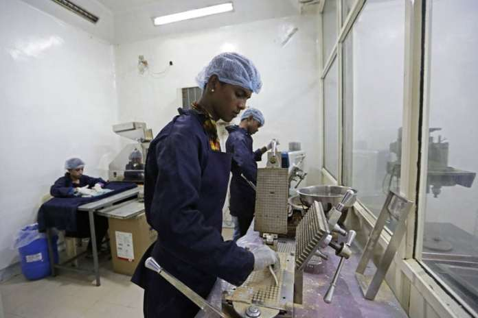 Workers of Jain Cow urine therapy and health clinic pour powdered cow urine onto capsules in a chamber of a factory in Indore