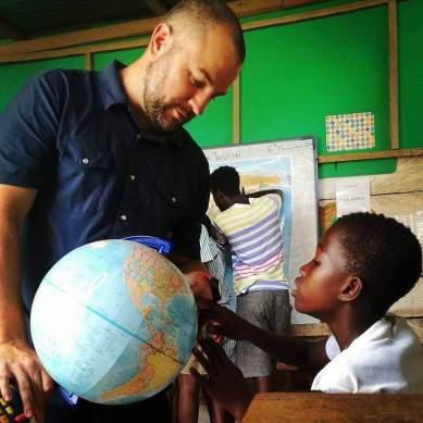 Justin showing a student where Ghana is on a globa
