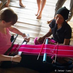 Thai woman showing a volunteer how to weave fabric