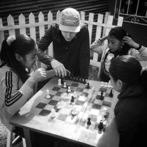 Volunteer and students playing chess in Peru