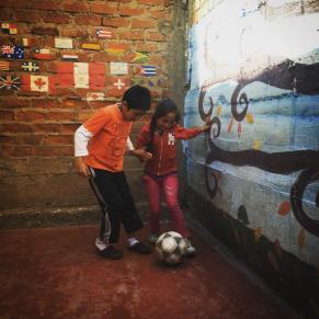 Kids playing fútbol in the garden