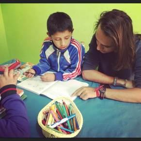 Volunteer helping child with his homework in Peru