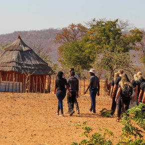 Volunteers and locals walking to a hut in Zambia