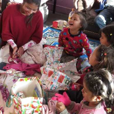 Project founder and kids opening gifts