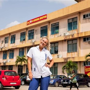 Midwife volunteer in Ghana posing in front of the hospital