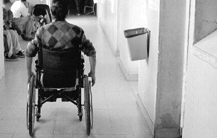 Persona en silla de ruedas avanza por un pasillo
