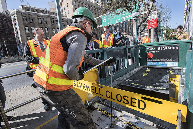 Photo of MTA employee deploying subway entrance flood prevention device