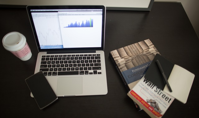 Open Laptop With Financial Statements And Textbooks Nearby
