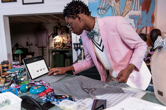 Moziah Bridges checking tablet while sewing bow ties