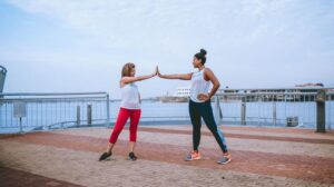 Two women high fiving on pier