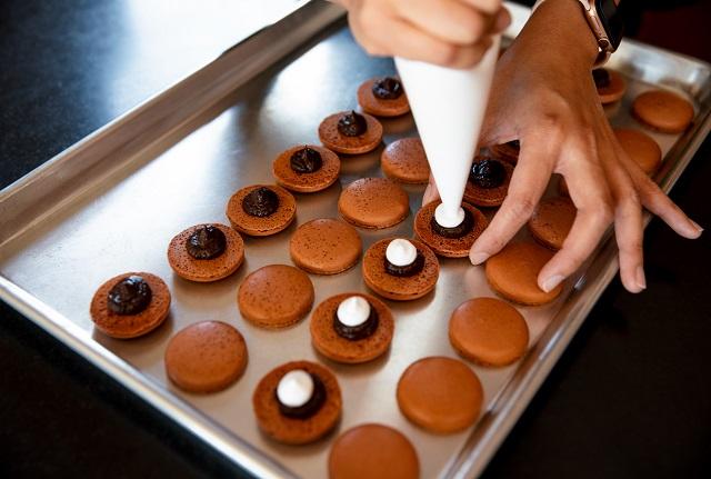 Anita Lee piping filling onto baked macarons