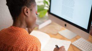Woman sitting at computer taking notes
