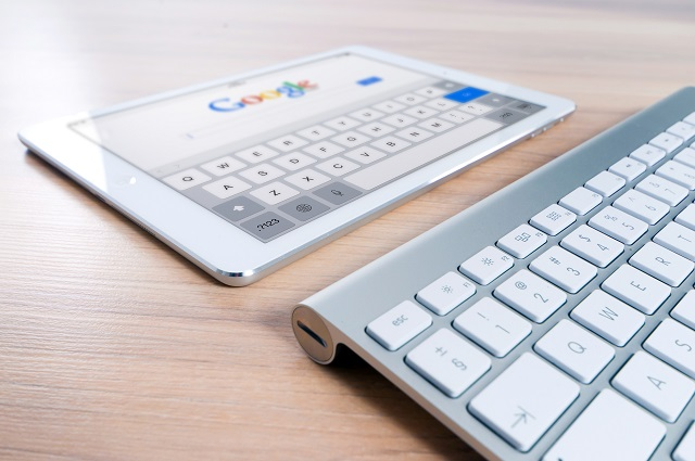 Tablet resting in front of a keyboard with a search page open