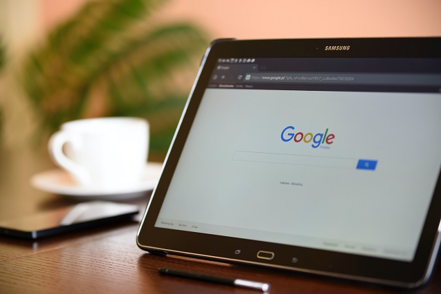 Tablet resting on a wooden table with Google search open