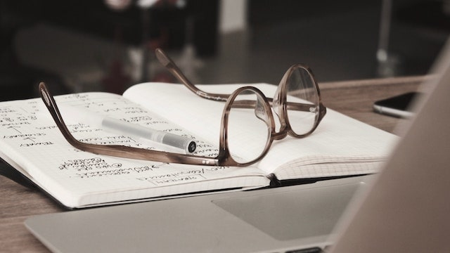 How To Become A Mentor Glasses Resting on Open Notebook Near Laptop