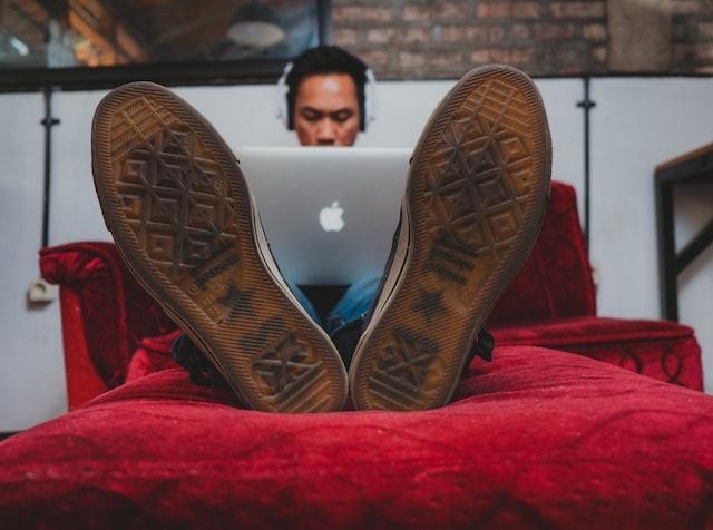 Man Working on Laptop on Sofa Illustrates Freelance Considerations