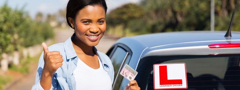 Girl holding driving licence and standing next to a learner can in east london