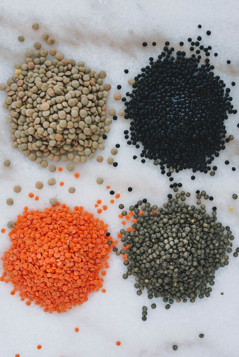 french green lentils, red lentils, green lentils, and black lentils on white marble counter