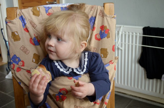 toddler eating sandwich in her totseat