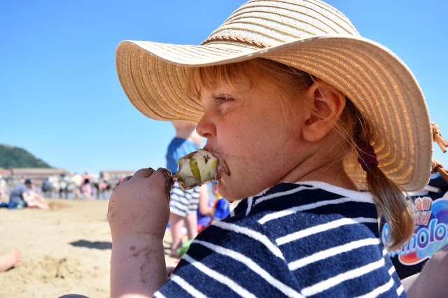 toddler eating lolly on the beach