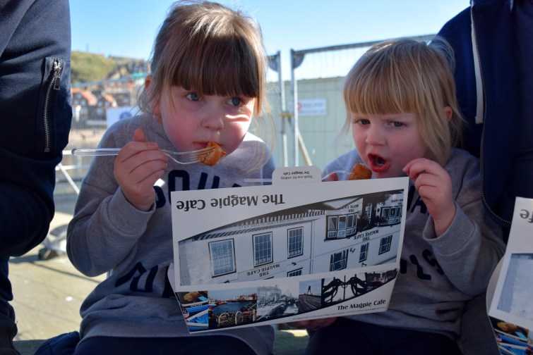 Girls eating chips from The Magpie Cafe, Whitby