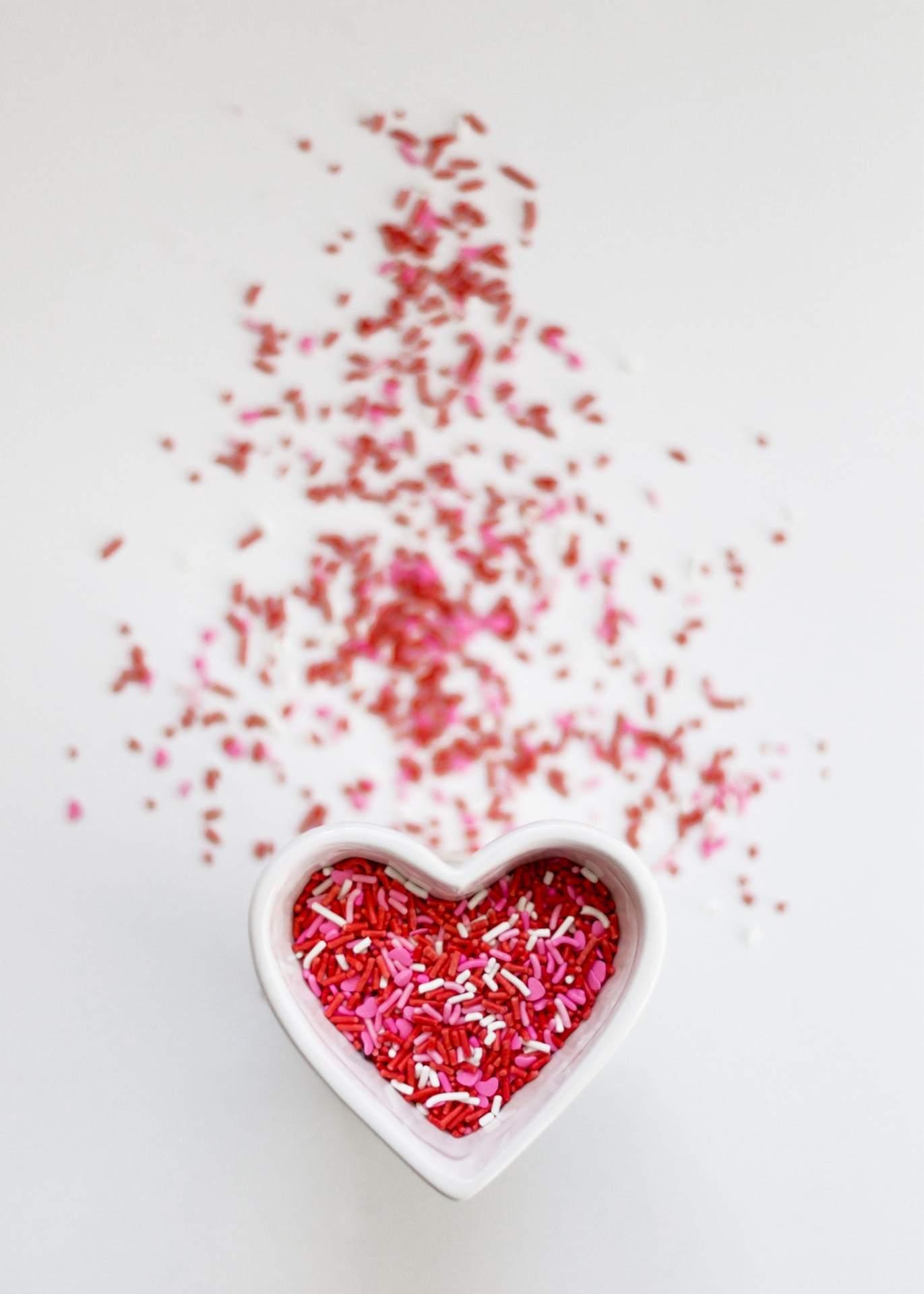 Rote Zuckerstreusel in weißer Schale in Herzform