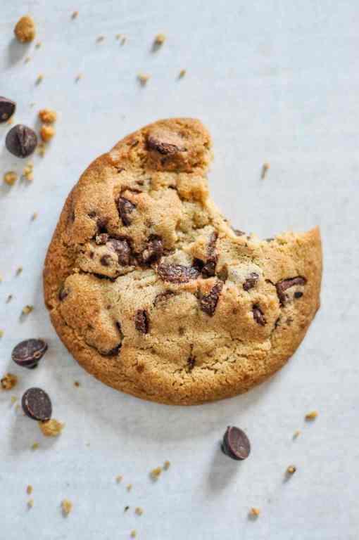 Ein angebissener Schoko-Cookie liegt auf einem Tisch.