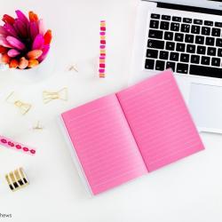 Ein Mac Book Air und Schreibutensilien auf einem weißen Schreibtisch. Photo by Emma Matthews on Unsplash.