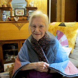 senior woman at home with a small quilt