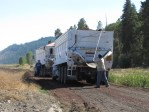 Two potato trucks are stopped to have their loads of potatoes tarped before entering the highway.