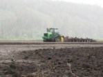 A John Deere 9620T pulling a disc in a rainy field at the Running Y Ranch in Klamath Falls, Oregon.