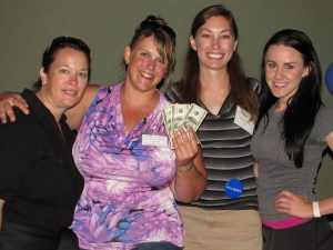 Maria Contreras, Tricia Hill, Katie Walker and Annie Sproule fanning the $400 prize they received for last place at the Gold Dust Open House Field Day golf scramble, which they later donated to Make-A-Wish Oregon.