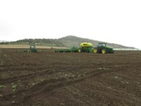 Three tractors with grain planting equipment in a field near Malin, OR.