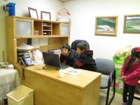 Nayeli Pena's son and step son, Hector and Carlos, watch a movie on a laptop at Gold Dust Potato Processors.