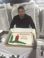 Santos Flores, HR manager at Gold Dust Potatoes, holds up a Christmas cake for the 2015 Holiday Luncheon held at Gold Dust's packing shed.