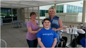 Make-A-Wish wish grantors Kay Ratliff and Jan Walker standing with Krue Johnston at Medford Regional Airport.