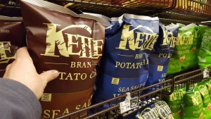 Consumer purchasing Kettle Brand potato chips at a store.