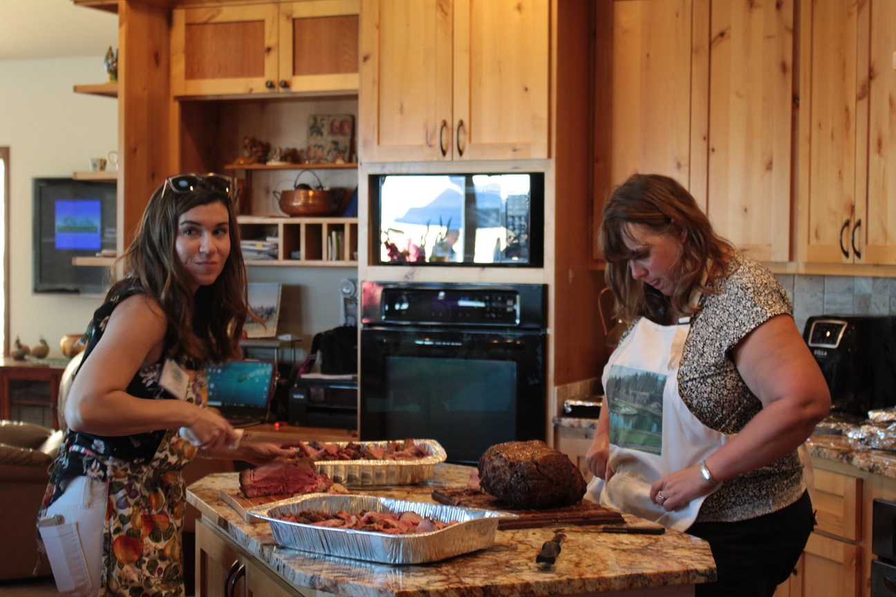 Lexi Crawford and Tricia Hill carving a roast for the Monday night Welcome Dinner before the 2019 Open House Field Day.