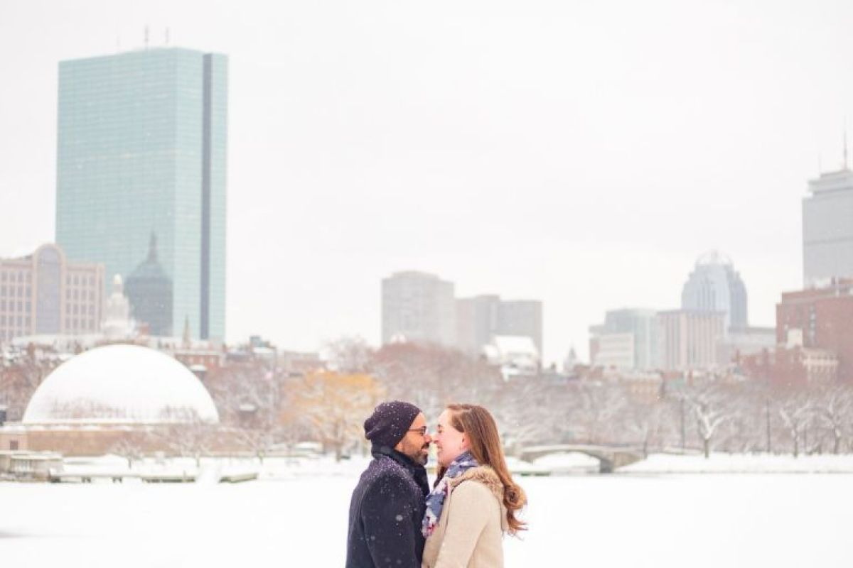 Engaged couple in winter coats nuzzles in the snow in front of the Boston Skyline near the Charles River