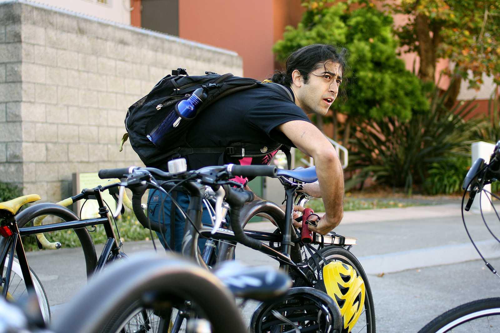 Shervin Sahba locks up his bike between Humanities and Creative Arts buildings Oct. 7, 2013. Photo by Tony Santos / Xpress