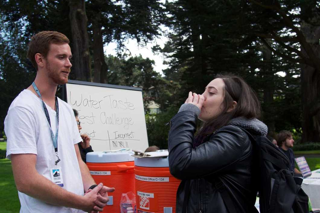 Cameron Bingley watches as Daisy Gerstein takes a water taste test challenge during the sustainability fair in the quad at SF State on Wednesday 23, 2013. Photo by Kate O'Neal / Xpress