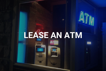 """The words """"Lease An ATM"""" are across the image in white. Night time, the photo is of the inside of an ATM store from the sidewalk. There are two ATMs lit up inside, and a bright blue neon """"ATM"""" sign hangs in the right corner of the room. Opposite the room, is a smaller red neon """"ATM"""" sign."""