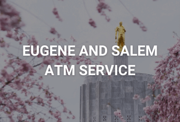"""The words """"Eugene and Salem ATM Service"""" are across the image in white. It is an overcast morning in early spring, the cherry blossoms are falling on screen. Two fuzzy cherry blossom trees are in the foreground. In the background stands a shining gold statute atop a linen grey government building."""
