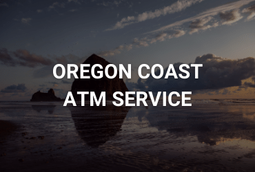 """The words """"Oregon Coast ATM Service"""" are across the image in white. The image is of the iconic canon beach rock that towers above near the ocean shoreline."""