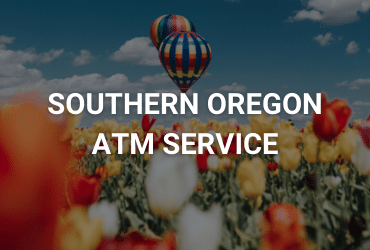 """The words """"Southern Oregon ATM Service"""" are across the image in white. In the foreground are blurry tulips in red, white, and yellow. In the background is a vibrant, colorful, stripped hot air balloon."""