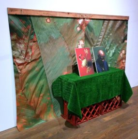 Fake grass and plastic crates displaying Vitturi's photographs instead of produce